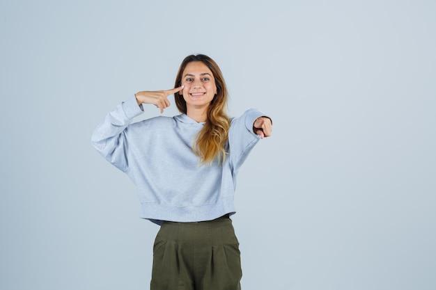Ragazza bionda che indica se stessa e la macchina fotografica con il dito indice in felpa e pantaloni blu verde oliva e sembra felice, vista frontale.