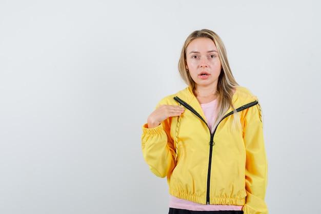 Ragazza bionda che indica se stessa in maglietta rosa e giacca gialla e sembra seducente.