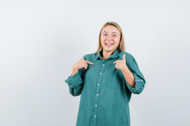 Ragazza bionda che indica se stessa con l'indice in camicetta verde e sembra felice