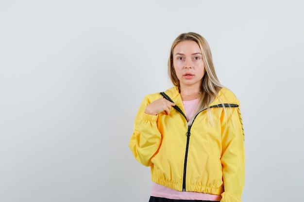 Ragazza bionda che indica se stessa in giacca gialla e sembra perplessa
