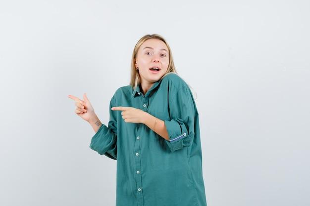 Ragazza bionda che punta a sinistra con l'indice in camicetta verde e sembra felice