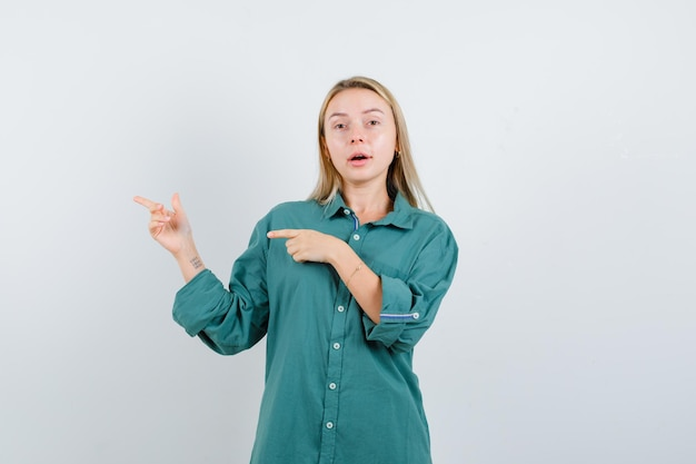 Ragazza bionda che punta a sinistra con l'indice in camicetta verde e sembra seria,