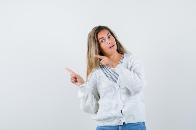스트라이프 티셔츠, 흰색 카디건 및 진 바지에 검지 손가락으로 왼쪽을 가리키는 금발 소녀와 매혹적인 찾고 있습니다. 전면보기.