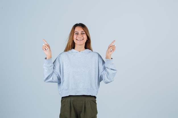 Blonde girl pointing opposite directions with index finger in olive green blue sweatshirt and pants and looking charming. front view.