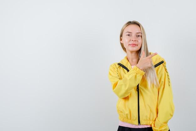 분홍색 티셔츠와 노란색 재킷에 오른쪽을 가리키고 행복을 찾는 금발 소녀.