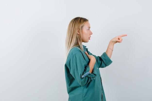 Блондинка, указывая вправо, держа руку на груди в зеленой блузке и глядя сосредоточенно.
