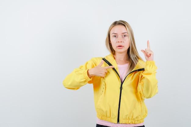Ragazza bionda che punta in alto e a destra con l'indice in maglietta rosa e giacca gialla e sembra seria.