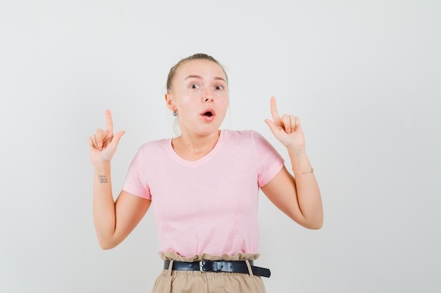 Ragazza bionda rivolta verso l'alto in t-shirt, pantaloni e sguardo spaventato, vista frontale.