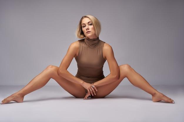Блондинка позирует на белом боди раздвинула ноги