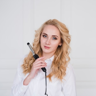 Blonde girl posing with curling iron