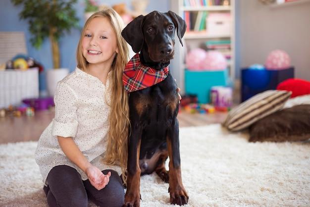 彼女の魅力的な犬とポーズをとるブロンドの女の子