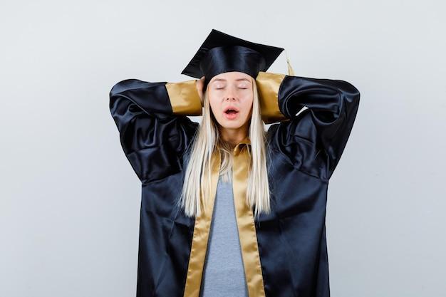 Ragazza bionda che preme le mani sulle orecchie in abito e berretto da laurea e sembra calma