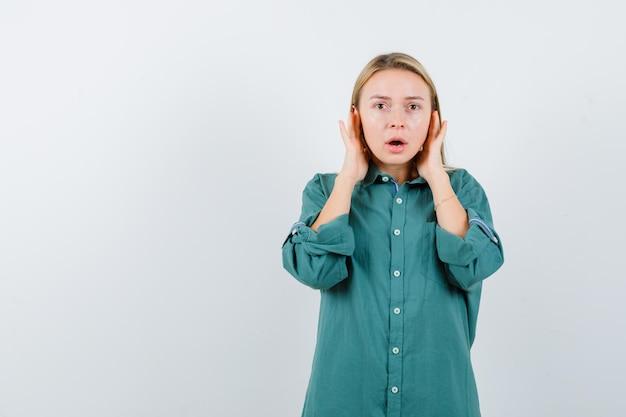 緑のブラウスで耳に手を押してショックを受けているブロンドの女の子