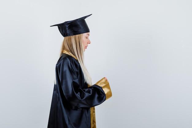 Ragazza bionda che finge di tenere qualcosa con entrambe le mani in abito da laurea e berretto e sembra carina.