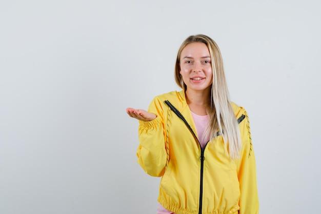黄色いジャケットに何かを持っているふりをして陽気に見えるブロンドの女の子。