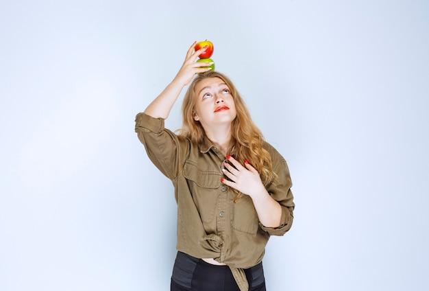 Блондинка кладет красный персик на голову.