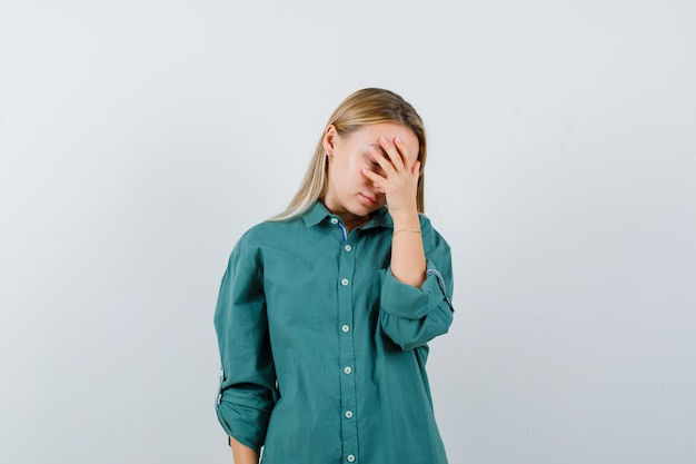 Blonde girl putting hand on eye in green blouse and looking tired.