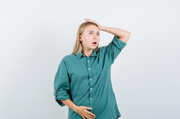 Ragazza bionda che mette la mano sopra la testa mentre tiene la mano sulla pancia in camicetta verde e sembra sorpresa