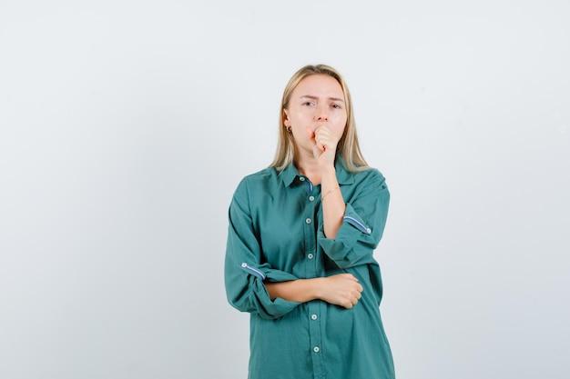 Ragazza bionda che mette la mano sulla bocca mentre tiene la mano sulla pancia in camicetta verde e sembra assonnata