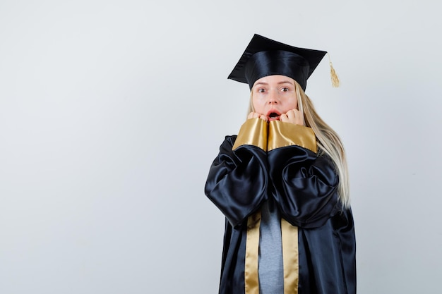 ブロンドの女の子が口の近くに手を置き、卒業式のガウンとキャップで口を開けて、驚いて見えます。
