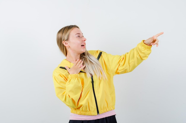 Блондинка положила руку на грудь, указывая вправо в розовой футболке и желтой куртке и выглядела удивленно.