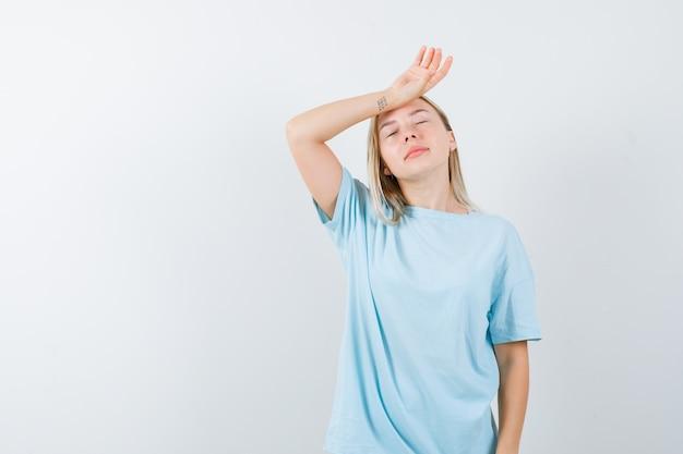 Блондинка положила руку на лоб, с головной болью в синей футболке и выглядела измученной. передний план.
