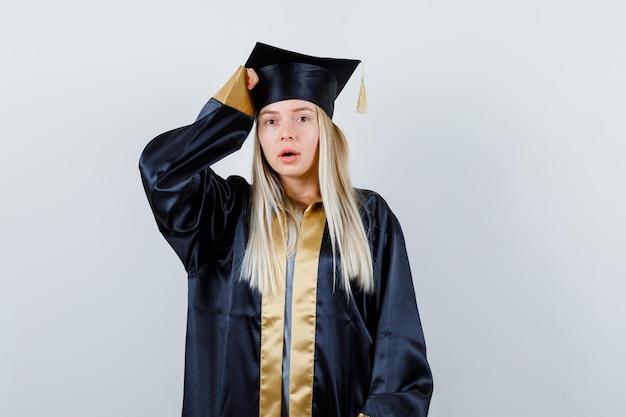 Блондинка положила руку на голову в выпускном платье и кепке и выглядела мило.