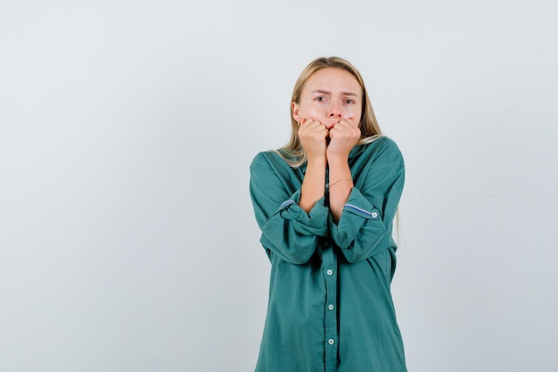 Blonde girl putting hands on mouth in green blouse and looking shocked
