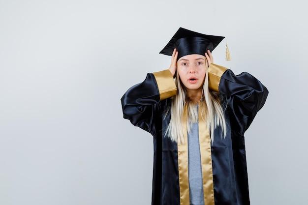 卒業式のガウンとキャップのキャップに手を置いて驚いて見えるブロンドの女の子