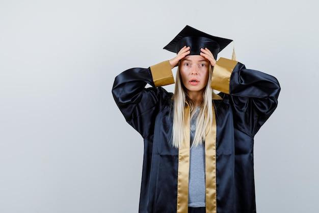 卒業式のガウンとキャップで額に手を置いて、驚いて見えるブロンドの女の子。