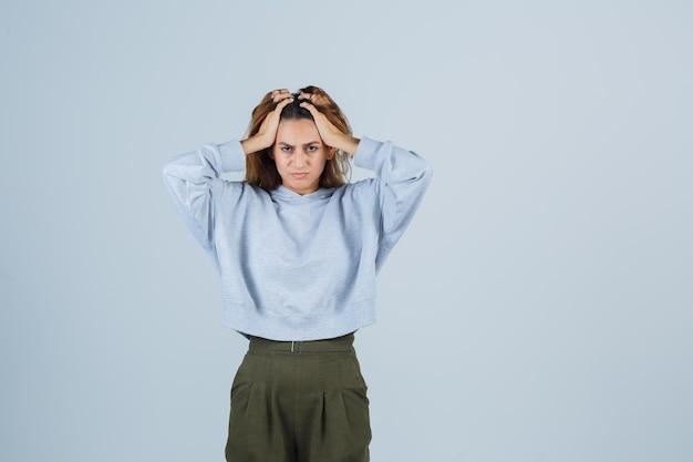 Блондинка кладет руки на голову в оливково-зеленом синем толстовке и брюках и выглядит усталой, вид спереди.