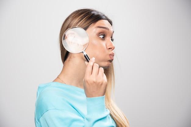 Ragazza bionda che mette una lente d'ingrandimento al suo orecchio.