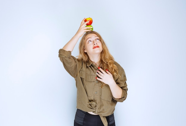 Blonde girl putting a red peach over her head.