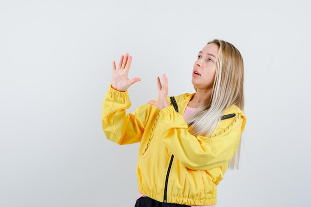 Blonde girl raising hands to defend herself in yellow jacket and looking scared