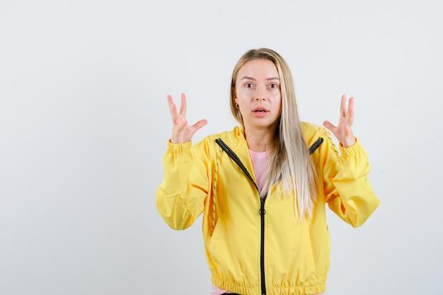 Blonde girl raising hands in puzzled gesture in yellow jacket