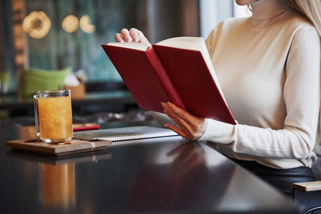 Blonde girl read a book with red cover in the restaurant with table and yellow drink on it