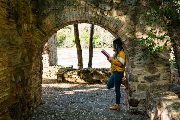 Blonde girl reading a book leaning on a stone arch. river bank. lifestyle concept.