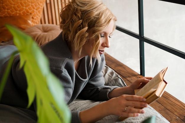 ベッドで本を読んでいるブロンドの女の子-緑の植物のある居心地の良い部屋