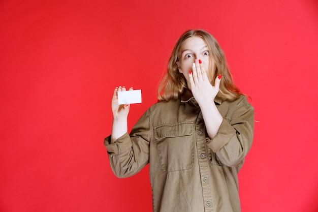 La ragazza bionda ha ricevuto un biglietto da visita ed è rimasta sorpresa.