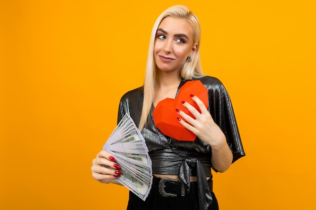 Blonde girl received a cash gift and holds a paper heart in his hands