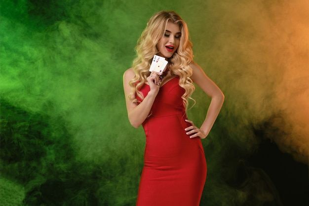 Blonde girl in red dress and necklace showing two playing cards smiling posing on colorful smoky bac...
