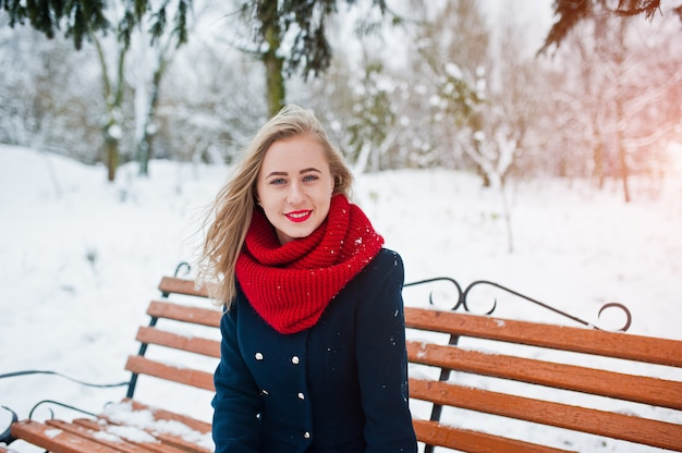 Blonde girl in red scarf and coat sitting at bench on winter day.