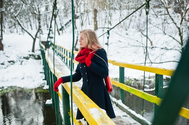 Blonde girl in red scarf and coat walking on bridge at park on winter day.