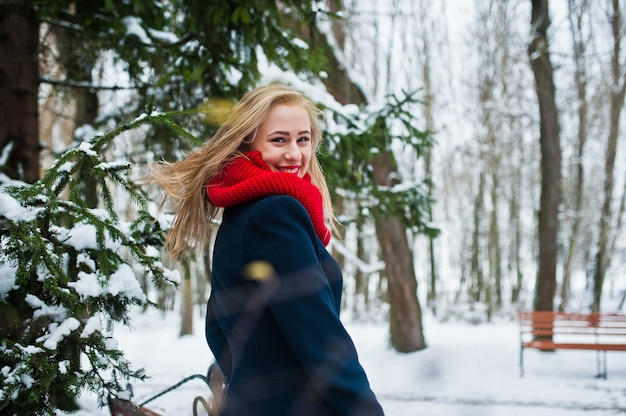 Blonde girl in red scarf and coat walking at park on winter day.