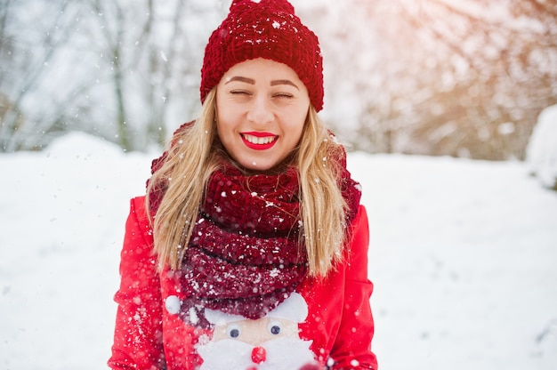 Blonde girl in red scarf, hat and santas sweater posing at park on winter day.