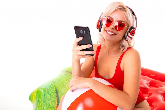 Blonde girl in a red swimsuit and sunglasses sitting on swimming mattress and listening to music on headphones and holding a phone in her hands