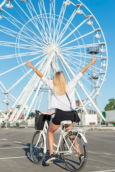 Blonde girl riding a bicycle next to a fun wheel