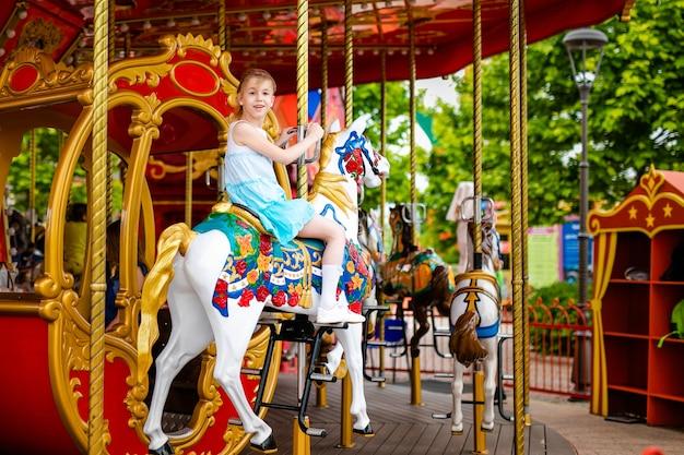 メリーゴーランドカルーセルでカラフルな馬に乗ってブロンドの女の子