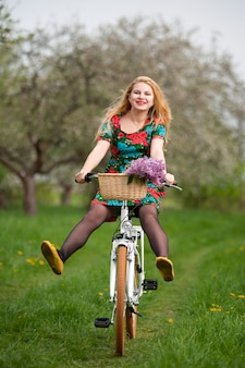Blonde girl riding a vintage bicycle with lifting legs