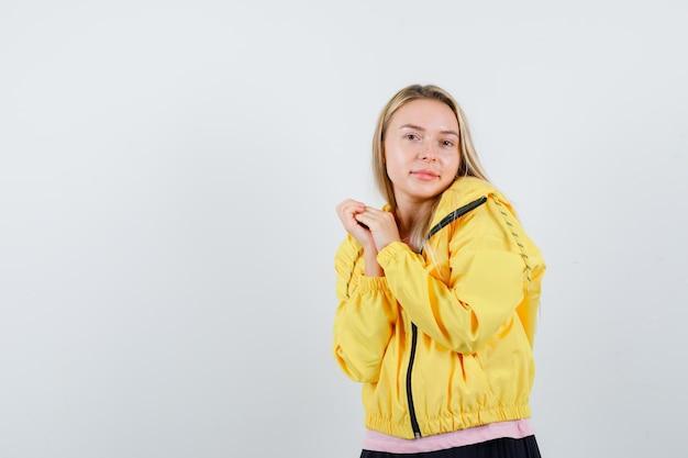 ピンクのtシャツと黄色のジャケットで手をこすり、魅力的に見えるブロンドの女の子。